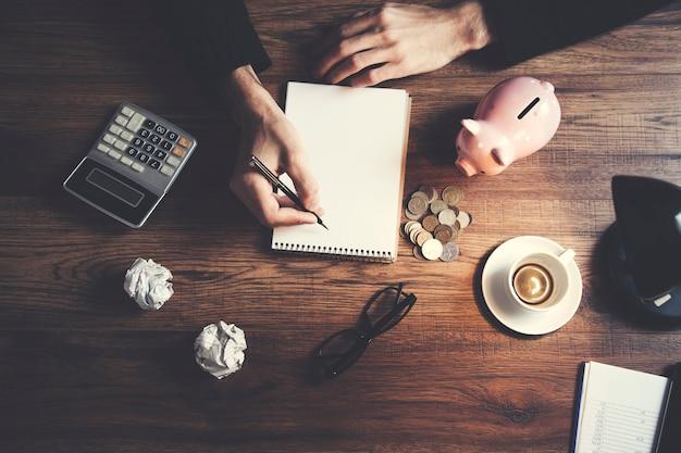 Homme écrit bloc-notes et tirelire sur table