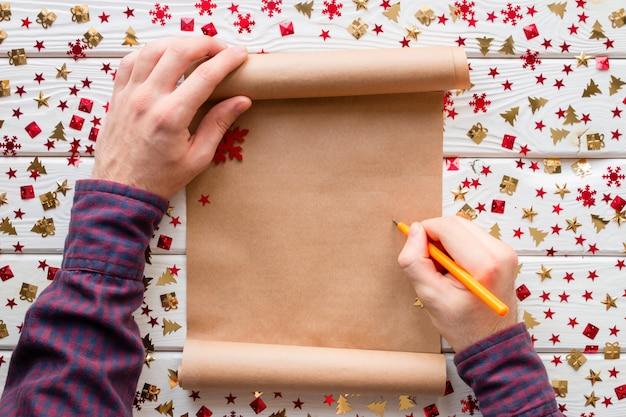 Homme écrit dans une liste de souhaits de noël