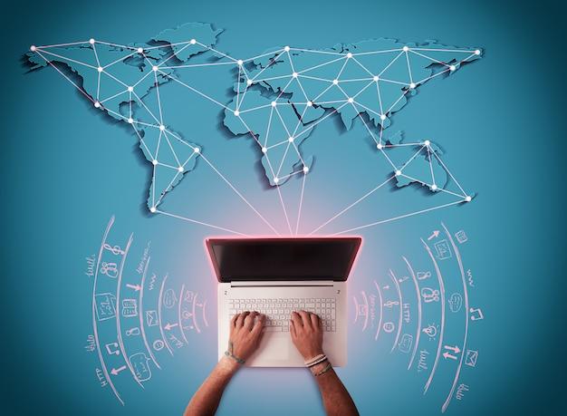L'homme écrit à l'ordinateur avec la carte du monde