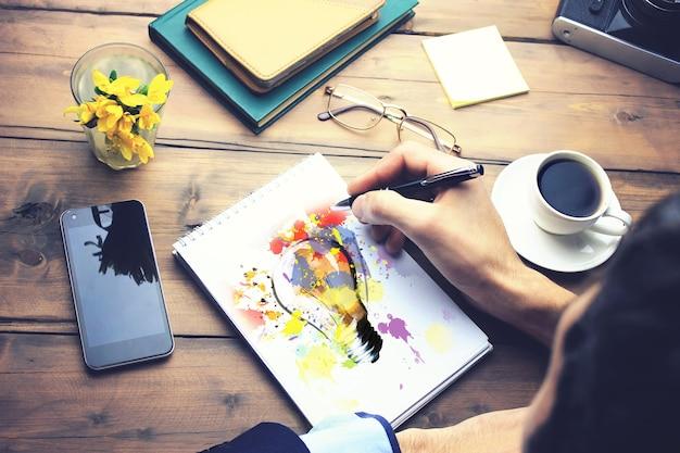 Homme écrit sur papier idée sur table de travail en bois