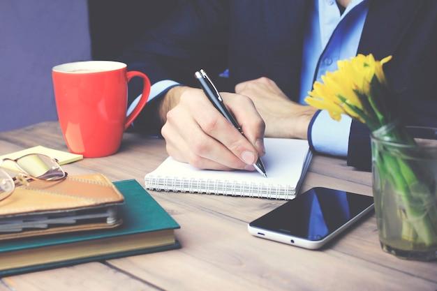 Homme écrit sur papier sur table de travail en bois
