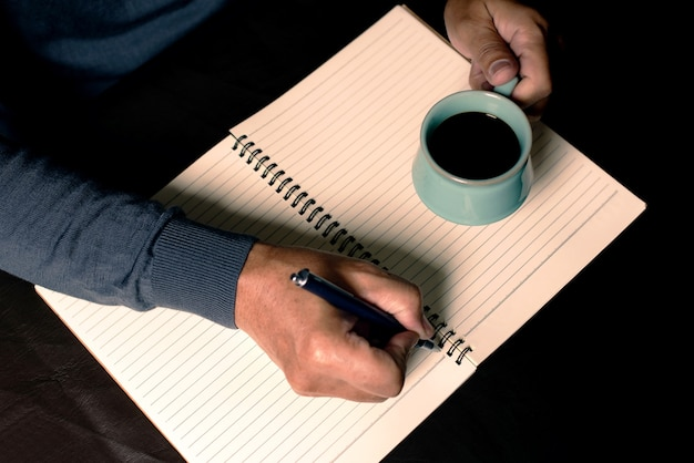 L'homme écrit avec un stylo sur un carnet et buvant du café noir.activités en journée libre