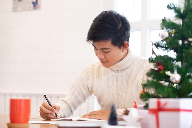 Homme écrivant des cartes de voeux de noël et du nouvel an.