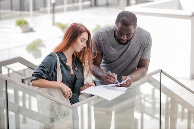Homme écrivant dans des papiers aidant femme