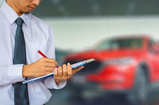 Homme écrivant la note sur l'arrière-plan flou de moteur de voiture. à noter, le transport