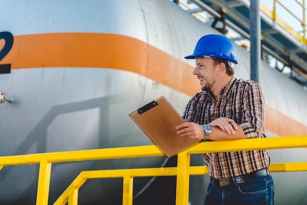 Homme écrivant des notes dans l'usine