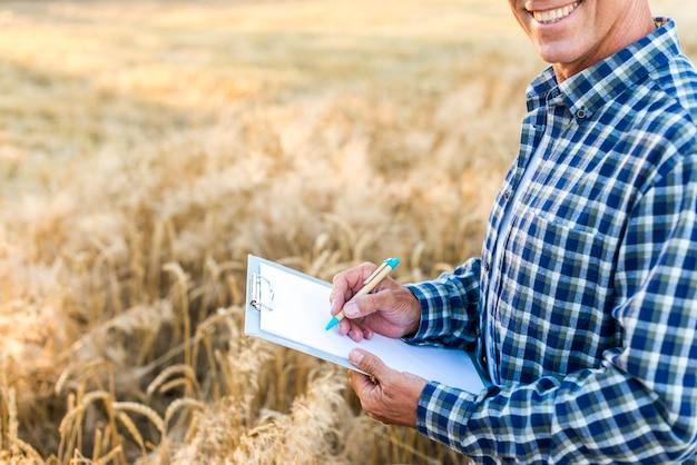 Homme écrivant sur un presse-papiers dans un champ de blé