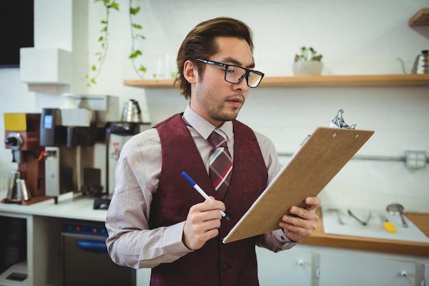 Homme écrivant avec un stylo sur le presse-papiers