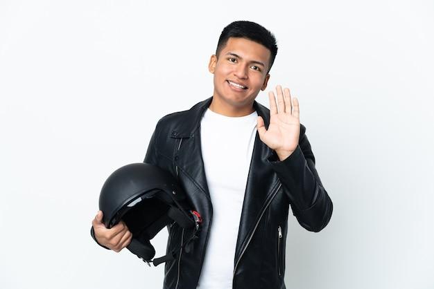Homme ecudorien avec un casque de moto isolé sur fond blanc saluant avec la main avec une expression heureuse