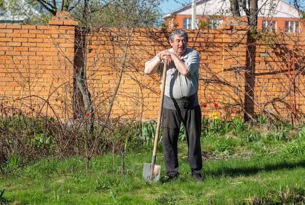 L'homme ederly avec ceinture de soutien dorsal s'appuie sur le manche d'une pelle et se repose après avoir creusé les lits dans le jardin