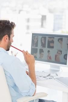 Homme éditeur de photos travaillant sur ordinateur au bureau