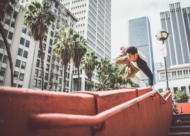 Homme effectuant des tours de parkour dans le centre urbain