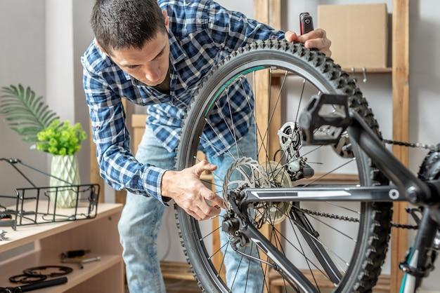 Un homme effectue l'entretien de son vélo de montagne. concept de fixation et de préparation du vélo pour la nouvelle saison