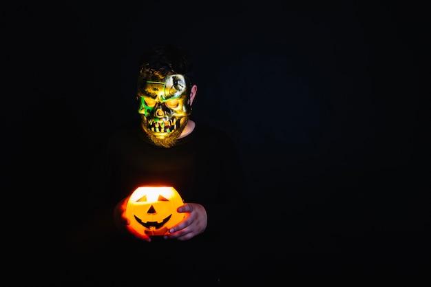 Homme effrayant avec une lanterne brûlante de halloween