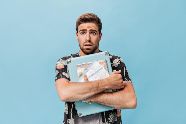 Homme effrayé aux yeux bleus et à la barbe en vêtements modernes d'été regardant à l'avant et tenant une valise fraîche sur un mur isolé