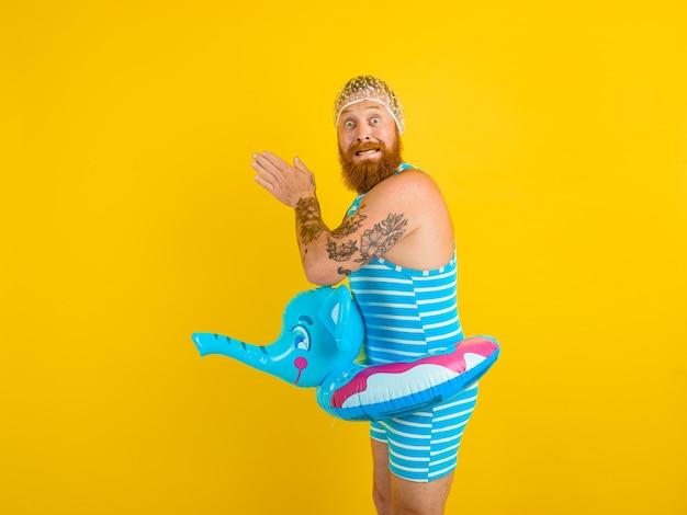 Un homme effrayé avec une bouée de sauvetage et un bonnet pour les femmes effrayées est prêt pour l'été