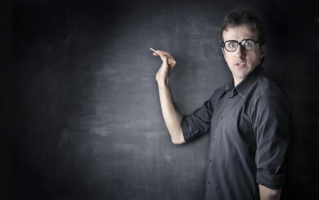 Homme effrayé écrivant sur un tableau noir