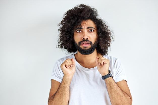 Un homme effrayé effrayé regarde la caméra, un gars d'apparence arabe en t-short blanc décontracté