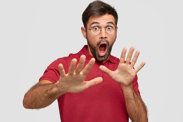 Homme effrayé avec une expression effrayée, des gestes avec les paumes, fait signe de la défense, s'exclame avec une expression étonnée