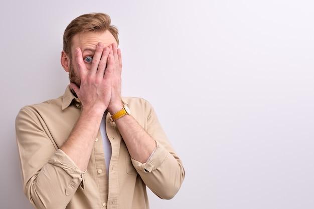 Homme effrayé peur de quelque chose qu'il a vu, isolé sur un mur blanc