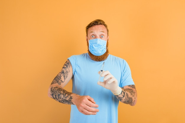 Un homme effrayé avec un tatouage de barbe et un masque pour covid est prêt pour le vaccin contre le virus