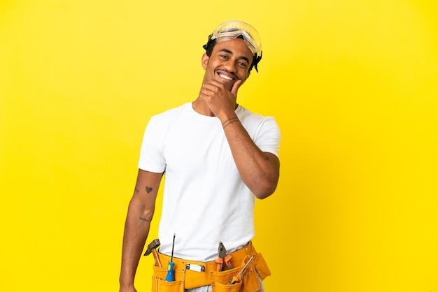 Homme électricien afro-américain sur mur jaune isolé heureux et souriant