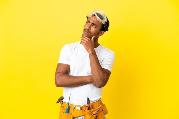 Homme électricien afro-américain sur mur jaune isolé et levant