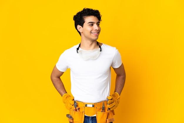 Homme électricien vénézuélien isolé sur fond jaune posant avec les bras à la hanche et souriant