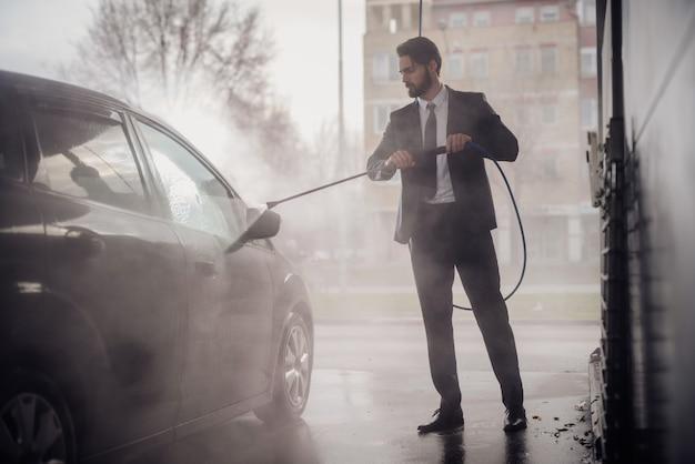 Homme élégamment discret lavant sa voiture dans le lavage de voiture.