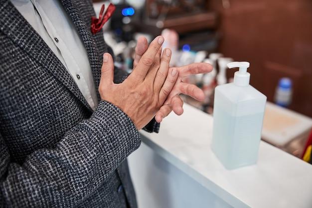 Un homme élégamment vêtu frottant le désinfectant d'une grande bouteille sur ses mains