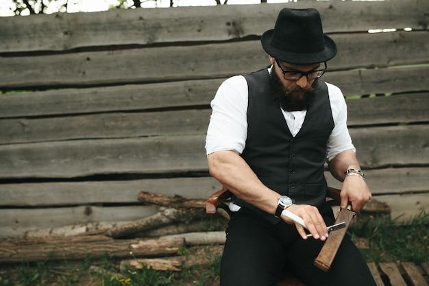 Homme élégant à aiguiser un rasoir
