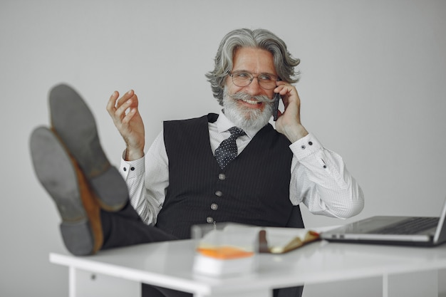 Homme élégant au bureau. homme d'affaires en chemise blanche. l'homme travaille avec le téléphone.