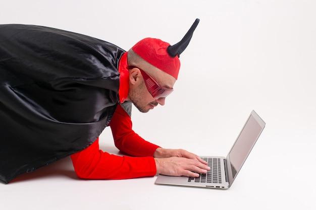 Homme élégant au chapeau de diable avec cornes et cape de vampire avec ordinateur portable