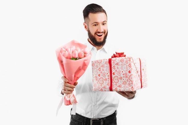Homme élégant avec une barbe tenant un bouquet de tulipes et une boîte cadeau, un cadeau pour la saint valentin