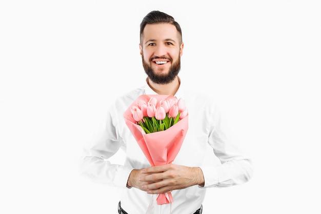 Homme élégant avec une barbe tenant un bouquet de tulipes, un cadeau pour la saint valentin