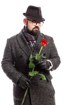 Homme élégant avec une barbe, vêtu d'un manteau élégant et d'un chapeau avec une rose rouge dans ses mains. isolé sur mur blanc. verticale.