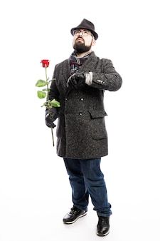 Homme élégant avec une barbe, vêtu d'un manteau élégant et d'un chapeau avec une rose rouge dans ses mains. pleine hauteur. isolé sur mur blanc. verticale.