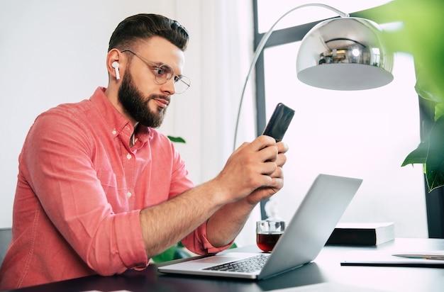 Homme élégant Barbu Confiant Et Heureux Dans Des Lunettes Et Des Vêtements Décontractés Intelligents Utilise Son Téléphone Intelligent. Photo Premium