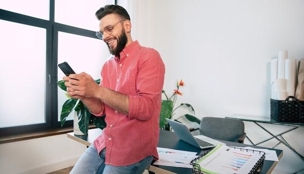 Homme élégant barbu confiant et heureux dans des lunettes et des vêtements décontractés intelligents utilise son téléphone intelligent.