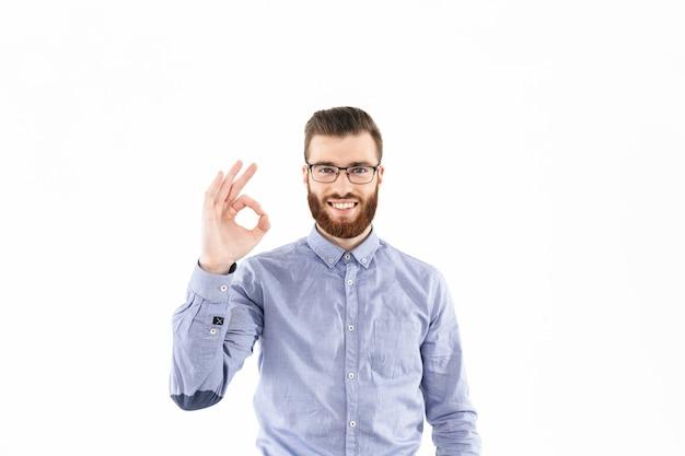 Homme élégant barbu souriant à lunettes montrant un signe ok et regardant