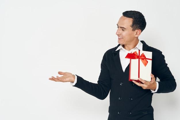 Homme élégant avec boîte-cadeau pointant sur la surface latérale