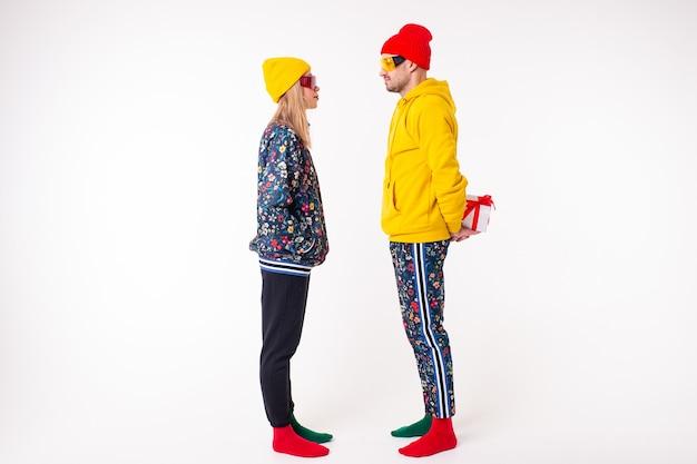 Homme élégant cachant un cadeau d'une petite amie dans des vêtements colorés
