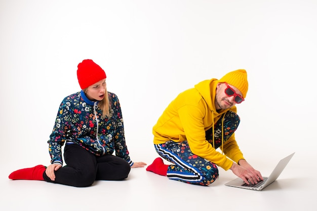 Homme élégant cachant l'écran de l'ordinateur portable de la femme dans des vêtements colorés