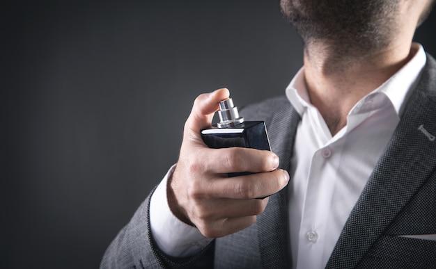 Homme élégant caucasien vaporisant du parfum.