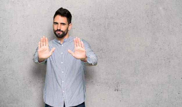 Homme élégant avec une chemise faisant un geste d'arrêt pour déçu par un avis sur un mur texturé