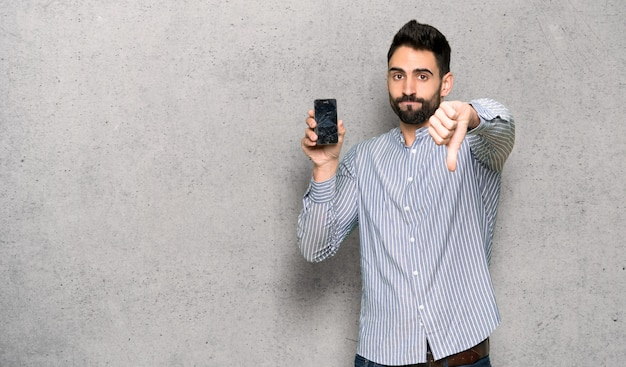 Homme élégant avec une chemise avec trouble tenant un smartphone cassé sur un mur texturé