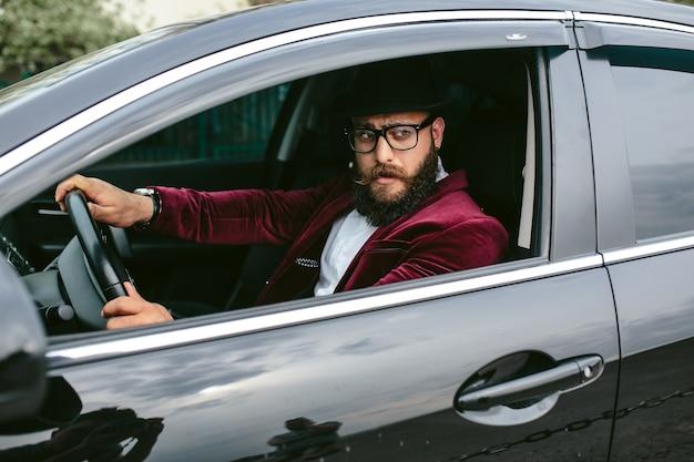 Homme élégant conduisant une voiture de luxe