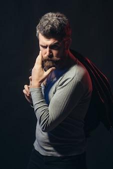 Un homme élégant et confiant avec barbe et moustache dans un élégant pull gris tient une veste en cuir noir sur l'épaule. homme pensif avec une coiffure élégante caressant sa barbe. isolé sur fond noir.