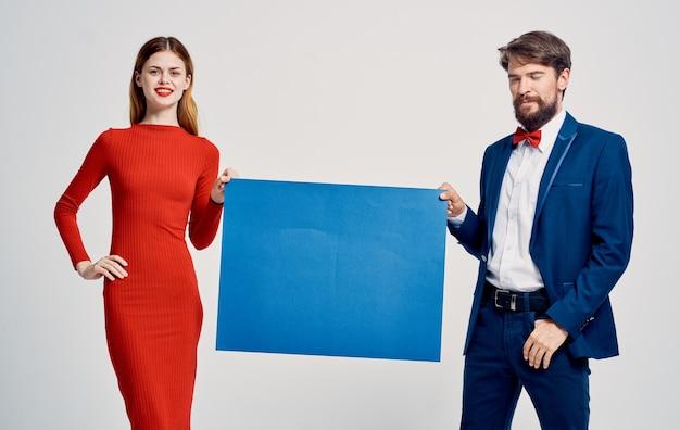 Un homme élégant en costume et une femme en robe rouge avec un coquelicot dans leurs mains une affiche pour une publicité
