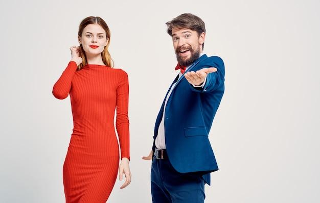 Un homme élégant en costume et une femme en robe rouge sur une publicité légère.